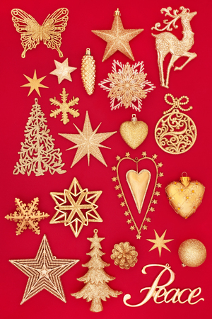 Luxury gold Christmas decorations with peace sign on red background. Traditional Christmas greeting card for the festive season.