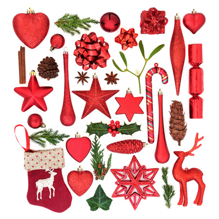 Red Christmas tree decorations, baubles, ornaments, symbols and winter flora on white background. Flat lay. Christmas card for the holiday season.