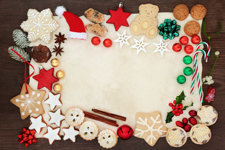 Christmas festive background border including tree decorations, biscuits, cakes, chocolates, spices and winter flora on parchment paper on rustic oak. Top view.