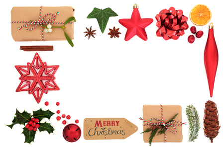 Christmas background border with festive symbols of tree decorations, food, winter flora, gift tag, ribbon and present on white. Flat lay.