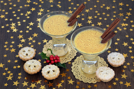 Christmas eggnog drink with traditional mince pies, gold star decorations and winter holly berries on rustic oak background. Festive theme. Stockfoto