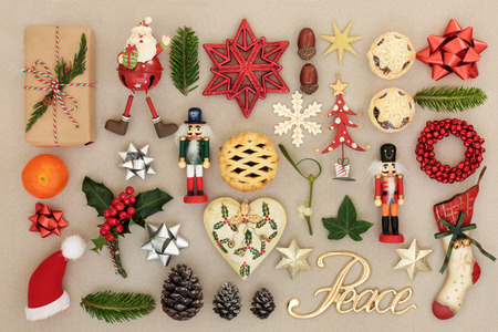 Christmas decorations with peace sign, food, flora, bows and traditional symbols forming an abstract background. Festive Christmas card for the holiday season. Top view.