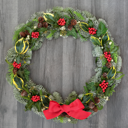 Christmas and winter wreath with holly, mistletoe, ivy, spruce fir, pine cones and a red bow on rustic grey wood  background. Stock Photo - 109810047
