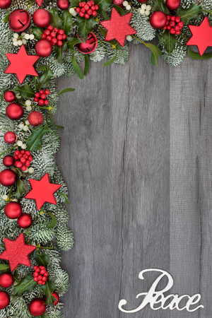 Christmas background border with silver peace sign and red star, ball and bell bauble decorations, holly, fir and mistletoe on rustic grey wood. Festive theme.