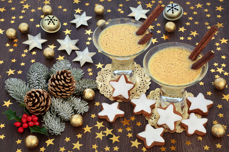 Traditional Christmas eggnog drink with gingerbread biscuits, gold star and bell decorations, foil wrapped chocolate balls with winter flora on rustic oak table background.