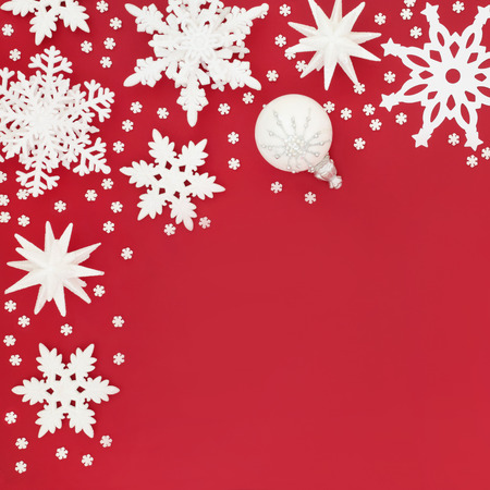 White and silver Christmas frosted bauble decorations on red background. Traditional Chistmas greeting card for the holiday season.