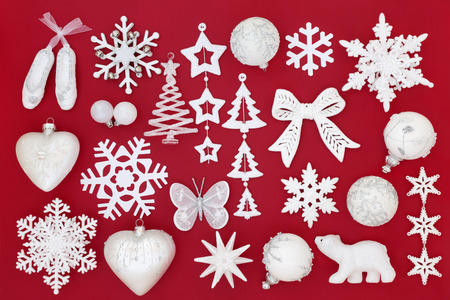 White and silver Christmas bauble decorations on red background. Traditional Christmas greeting card for the holiday season.