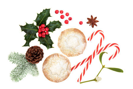 Christmas symbols with mince pie tarts, winter flora of holly, snow covered fir, pine cone, candy canes and star anise on white background. Top view. Stock Photo