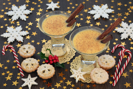 Christmas celebration with eggnog, mince pies, candy canes, star and snowflake decorations with winter holly on rustic oak table background. Festive theme. Stockfoto