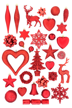 Red Christmas tree decorations, ornaments and symbols for the festive season on white background. Flat lay. Stock Photo
