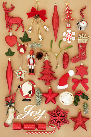 Christmas joy sign with retro bauble tree decorations and ornaments with winter flora and traditional symbols of the festive season  background. Top view. Stock Photo
