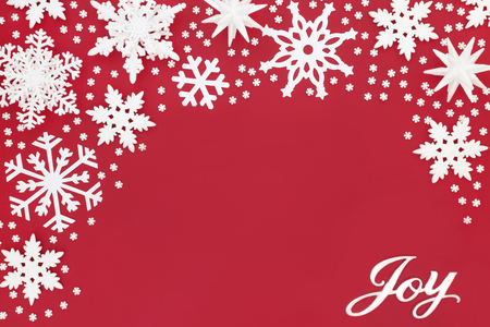 Christmas joy sign with sparkling white snowflake bauble decorations on red background. Traditional Christmas greeting card for the festive season.