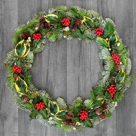 Traditional winter and Christmas natural wreath with holly, snow covered spruce pine fir, mistletoe, pine cones, cedar and ivy leaves on rustic grey wood  background.