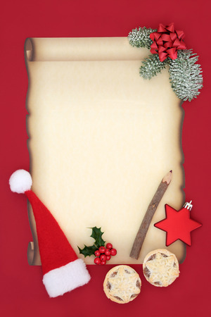 Letter to Father Christmas or invitation with blank parchment paper, santa hat, mince pies, pencil, bow, star bauble and winter flora on red background. Christmas Eve concept. Stock Photo