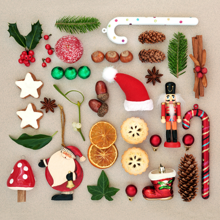 Traditional symbols of Christmas selection with food, old fashioned retro decorations and winter flora with berries, leaf sprigs and natural objects. Stock Photo