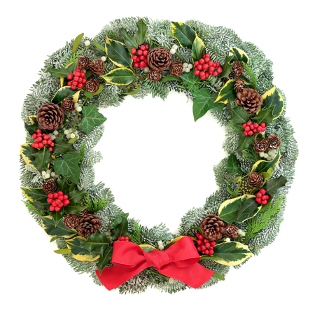 Winter and Christmas wreath with snow covered spruce pine fir, red bow, mistletoe, pine cones, cedar and ivy leaves isolated on white background.