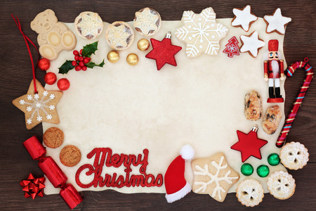 Merry Christmas background border with sign, tree decorations, biscuits, cakes, winter flora and chocolates in foil on parchment paper on rustic wood.