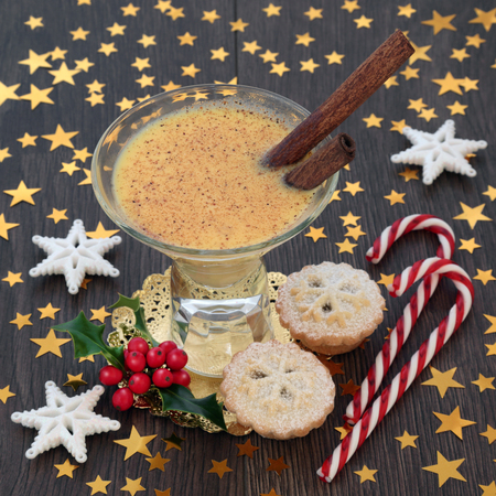 Christmas eggnog traditional drink with mince pies, candy canes, star decorations and winter holly on rustic oak table background. Festive theme.