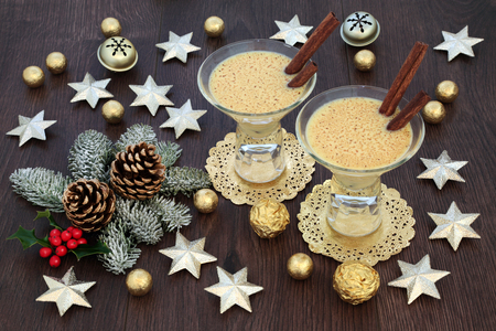 Traditional eggnog Christmas drink with gold star and bell decorations, foil wrapped chocolate balls, with winter flora of holly, fir and pine cones on rustic oak table background. Stockfoto