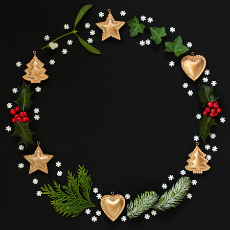 Christmas minimalist wreath garland with winter flora, gold bauble decorations and snowflakes on black background. Flat lay. Christmas card for the festive season. Imagens