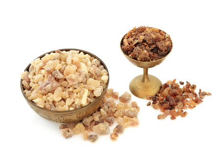 Frankincense and myrrh aromatic gum resin in old metal bowls and loose on white background.