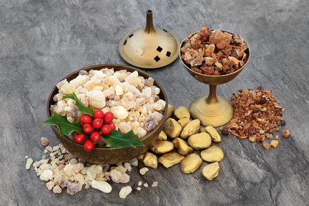 Gold frankincense and myrrh with holly, religious concept of gifts of the three wise men at Christmas celebrating the birth of Christ.