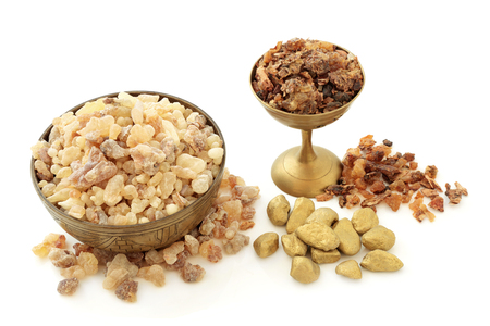 Gold Frankincense and myrrh aromatic gum resin in old metal bowls and loose on white background.