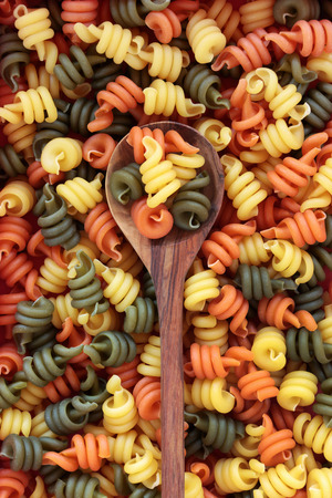 Trotolle tricolour pasta on an olive wood spoon and loose forming an abstract background.