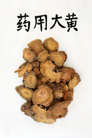 Rhubarb root herb used in chinese herbal medicine with calligraphy script, used as a laxative, regulates weight loss & helps treat type 2 diabetes. Translation reads as chinese rhubarb. Da huang. Stock fotó