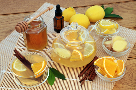 Flu and cold remedy herbal medicine ingredients with ginger, cinnamon, eucalyptus oil, lemon and orange fruit, honey and hot drink in glass tea cup and tea pot on bamboo. Фото со стока