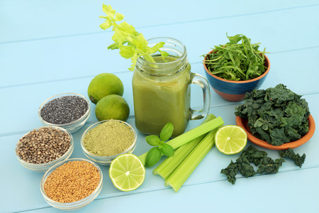 Health food vegetable smoothie juice drink with kale, celery, rucola, matcha powder, flax, chia & hemp seed on blue wood background. High in omega 3, antiioxidants, vitamins and dietary fibre.
