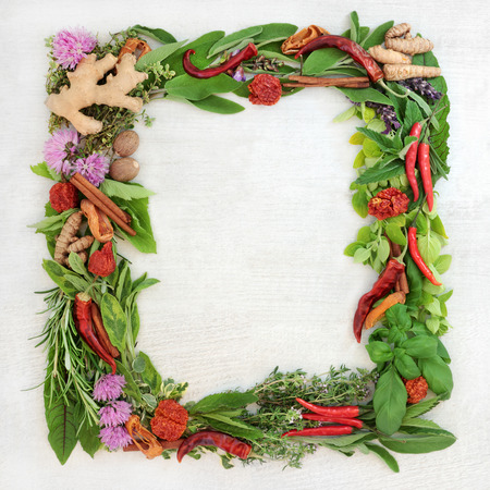 Herb leaf and spice wreath with a selection of fresh herbs with flowers on rustic wood background with copy space. Imagens