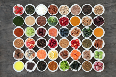 Super food to slow down the ageing process concept including fruit,vegetables,seeds, nuts, herbs, spices, green teas and dairy. High in antioxidants, anthocyanins, dietary fibre and omega 3. Top view on slate.
