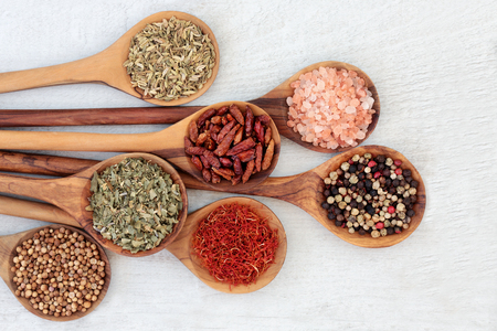 Herb and spice food seasoning in olive wood spoons with coriander seed, saffron, herbs de provence, peppercorns, chili peppers, himalayan salt and fennel. Left to right on rustic wood background.  Top view. Stok Fotoğraf
