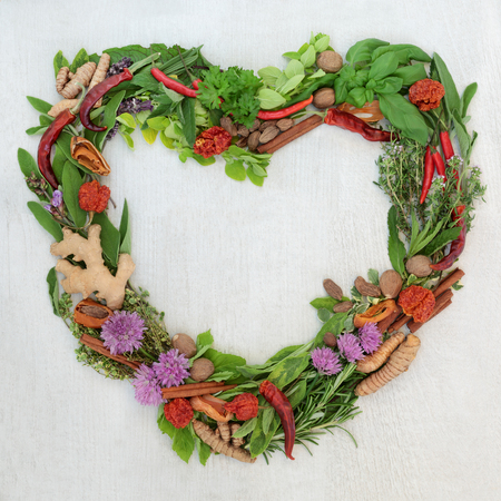 Heart shaped herb leaf and spice wreath with a selection of fresh herbs and spices with flowers on rustic white wood  with copy space.