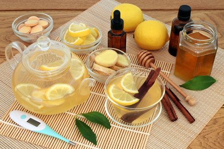 Medicinal cold and flu remedy with thermometer, eucalyptus and tea tree oil, ginger, cinnamon sticks, vitamin c tablets, lemon fruit and honey with hot drink on bamboo and oak.