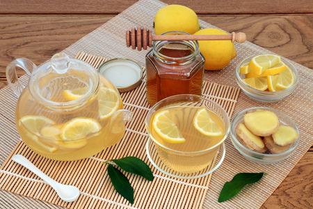 Koude en griep remedie geneeskrachtige ingrediënten met gemberkruid, citroenfruit, honing en warme drank in een glazen beker en theepot op bamboe en eiken achtergrond. Stockfoto