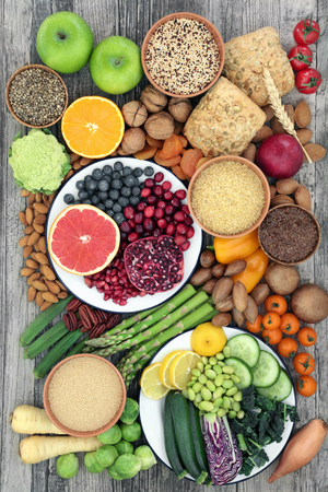 High fibre health food concept with vegetables,fruit. nuts, seeds, grains and whole grain seeded rolls. Foods with antioxidants, anthocyanins, vitamins and minerals. Top view on rustic wood.