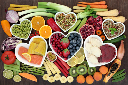 Weight loss health food concept with fresh vegetables, fruit, grain and seed salads, meat and fish with foods high in dietary fibre, antioxidants, vitamins and anthocyanins. Top view on oak wood.