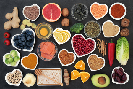 Súper alimento para retrasar el concepto de proceso de envejecimiento que incluye pescado, frutas, verduras, hierbas, especias, suplementos en polvo, miel y lácteos en pizarra. Alto contenido de antioxidantes, antocianinas, fibra dietética y vitaminas.