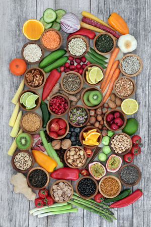 Super food concept for healthy eating including fruit, vegetables, cereals, nuts, seeds, herbs, spices and legumes, Foods high in antioxidants, anthocyanins, dietary fibre and vitamins.