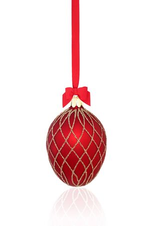 Luxury red and gold christmas tree bauble decoration with bow and ribbon on white background with reflection and copy space.