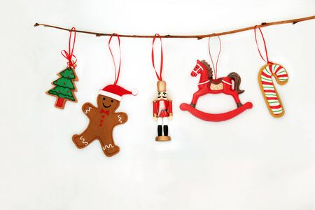 Christmas decorations hanging on a branch with nutcracker soldier, tree, candy cane and gingerbread man on   white background with copy space. Фото со стока