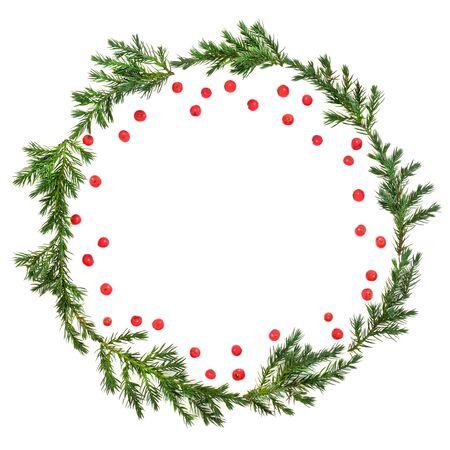 Winter- und Weihnachtswacholdertannenkranz mit losen roten Stechpalmenbeeren auf weißem Hintergrund mit Kopienraum. Traditionelles Symbol für die festliche Jahreszeit. Juniperis chinensis.