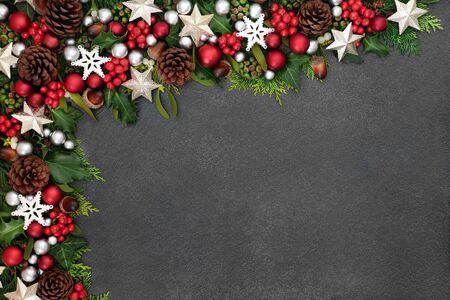 Festive Christmas background border with star and ball baubles, holly, mistletoe and winter flora on grunge grey background with copy space. Stock Photo