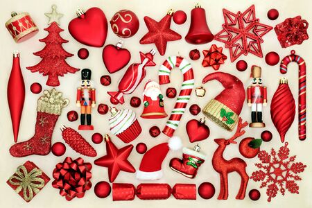 Large collection of red Christmas tree decorations on cream background. Stock Photo