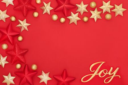 Christmas background with gold joy sign, star and bauble decorations on red forming an abstract border with copy space. Traditional greetings card for the festive season.