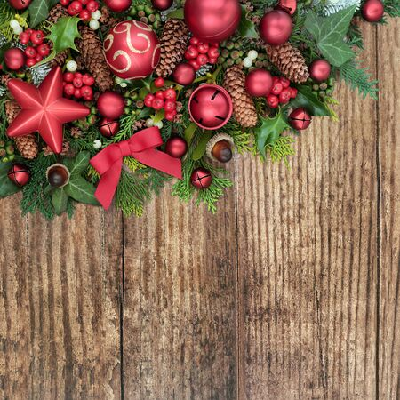 Christmas festive background border with festive bauble decorations and winter fora on rustic wood with copy space. Stock Photo