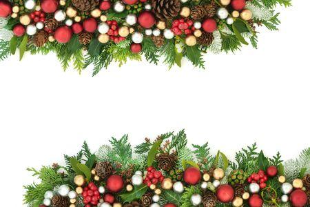 Feestelijke kerstachtergrond met rode, zilveren en gouden kerstversieringen en winterflora met dennenappels op wit met kopieerruimte.