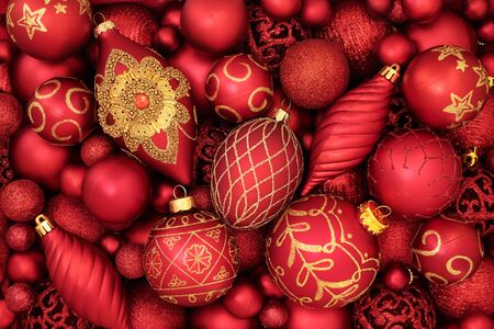 Red and gold Christmas tree bauble decorations forming an abstract background. Traditional theme with symbols for the holiday season.